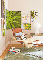 A sheepskin rug and cushions on a leather armchair with a matching footstool in the corner of a room with pictures of plants on the wall