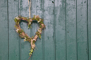 Heart-shaped wreath of birch twigs, hay, box, bark, waxflowers and raffia