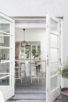 Blick durch geöffnete Terrassentür auf Esstisch mit Hockern