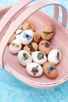 Easter eggs decorated with stickers in trug basket