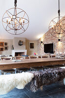 Sheepskins on bench at dining table in converted barn