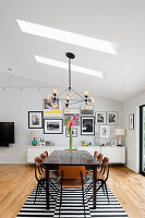 Dining area featuring skylights, low sideboard and gallery of pictures