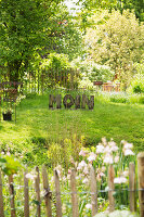 View over fence into summery garden with dialect greeting made from wooden letters on green lawn