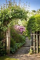 Natursteinweg führt durch berankten Torbogen in sommerlichen Garten