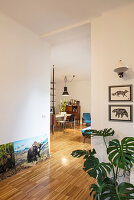Pictures of animals and rubber plant next to open doorway with view of dining area