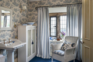 Pedestal sink, wicker armchair and toile de jouy wallpaper in blue and white bathroom