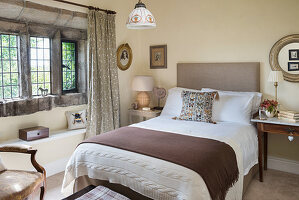 Double bed in bedroom with rustic stone window
