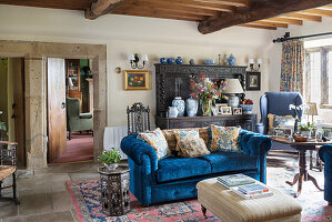 Scatter cushions on blue sofa and antique dresser in rustic living room wit wood-beamed ceiling