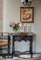 Vase of roses, wooden box and candles on antique console table with carved ornamentation