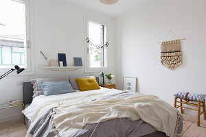 Double bed and hand-made wall hanging on white wall in bedroom