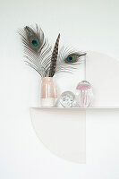 Feathers in jug on artistic metal shelf