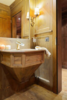 Luxurious bathroom panelled in wood with panelled sink