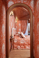 Opulent bedroom with identical orange pattern on wallpaper and fabrics
