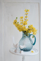 Forsythia in glass jug and bird figurines