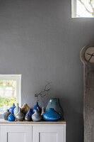 Collection of blue and grey vases against grey wall