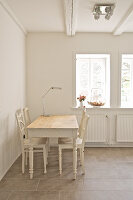 Weißer Holztisch mit Stühlen in Zimmerecke