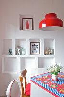 Tisch mit bunter Tischdecke, darüber rote Pendelleuchte, Stühle und Wandnischen in der Küche