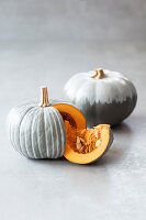 Pumpkins painted grey with white stripes and grey ombré