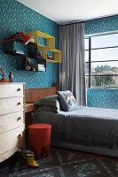 Shelving modules above bed in child's bedroom with blue-patterned wallpaper
