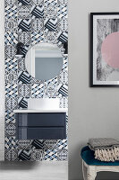 Geometric tiles in bathroom, washstand with countertop sink and round mirror