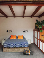 Bed linen with zigzag pattern in bedroom with wooden ceiling beams