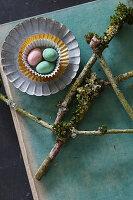 Ostereier in Pralinenformen neben Ästen mit Moos und Flechten