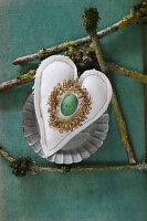 Grünes Ei und goldenes Kränzchen auf einem genähten Stoffherz