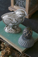 Küken-Backform aus Metall neben bemaltem Ei in der Guglhupfform