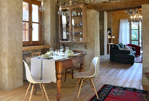 Antique dining table, classic chairs and glass-fronted cabinet in converted barn