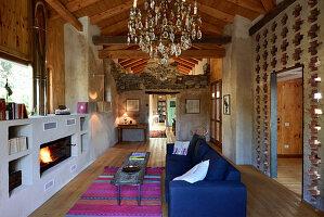 Loungebereich mit Kamin in umgebauter Scheune mit Beton-, Ziegel und Holzwänden
