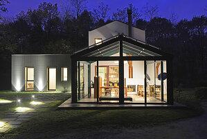 Haus mit Glasfassade in Abendbeleuchtung