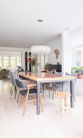 Long, colourful table and grey chairs in bright dining area