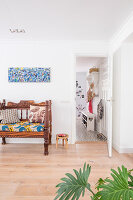Colourful cushions on wooden bench below colourful painting on living room wall