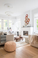 Pale seating, Moroccan pouffe, coffee table and fireplace in living room