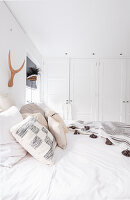 Double bed and fitted wardrobes in white bedroom