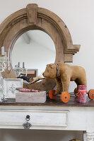 Ein alter Spielzeugbär auf Rollen vor einem ovalen Spiegel mit Holzrahmen