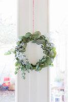 Wreath of eucalyptus branches and gypsophila on door