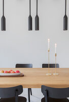 Black pendant lamps above dining table and black chairs