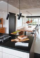 Brot auf der Kücheninsel, Blick über den Esstisch mit Holzplatte