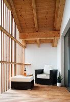 Sessel und Hocker auf überdachtem Balkon mit offener Fassade