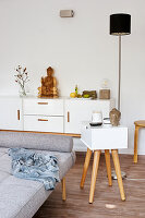 Modern side table with drawer next to grey couch