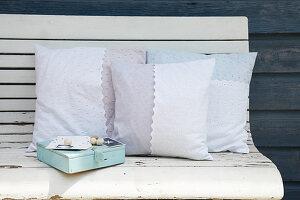 Kissen mit selbst genähten Kissenbezügen auf Holzbank