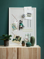 A homemade memo board made from a perforated board and rubber strings