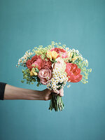 A hand holding a bunch roses, peonies, fresias and camomile