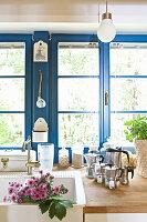 Landhausküche mit blauen Fenstern, Spülbecken und Espressokannen