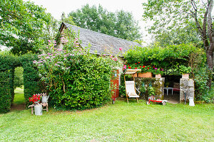 Old barn and roofed seating area in idyllic garden