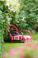 Roter Liegestuhl aus Rattan im Garten