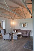 Gemütliche Polstermöbel vor halbhoher Raumteiler in umgebautem Stall mit Dachkonstruktion aus Holz