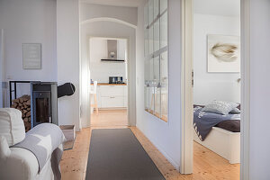 Converted dairy: Corridor between living room with log burner and bedroom with restored stable window in partition wall