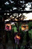 Handmade candle lanterns decorated with lavender hung from fence